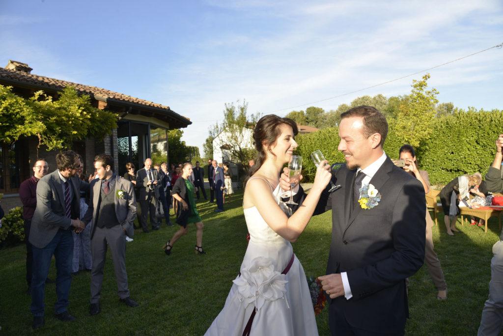 Gli sposi si guardano e brindano mentre gli invitati ballano in giardino