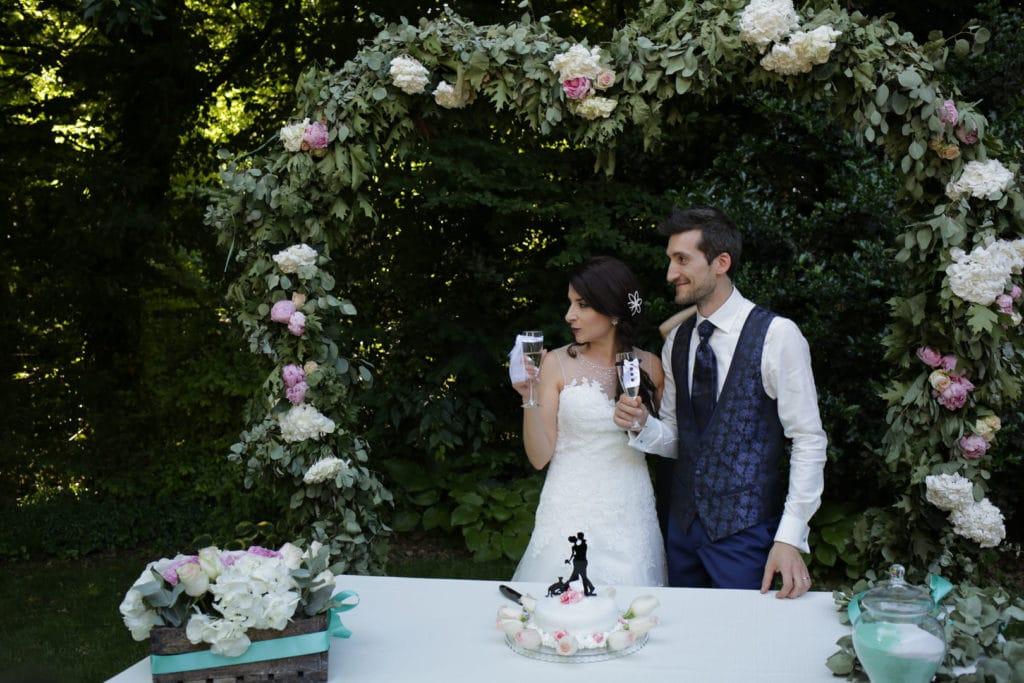 sposi-felici-taglio-della-torta-nel-giardino-dcon-decorazioni-floreali