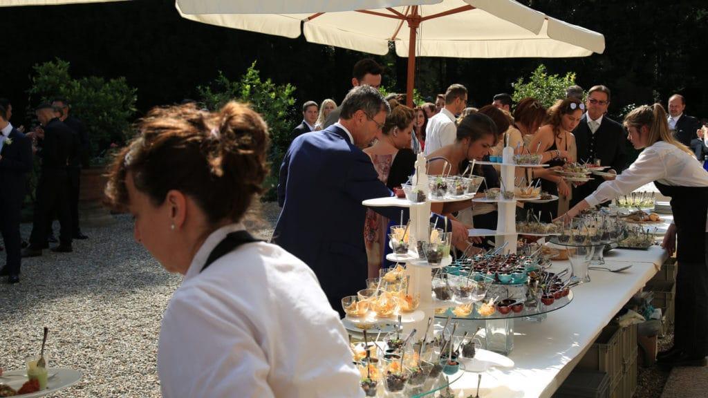 Invitati si servono al buffet nuziale in giardino con l'aiuto dei camerieri