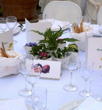 Tavola nuziale apparecchiata con piatti, calici di vetro e sculture vegetali