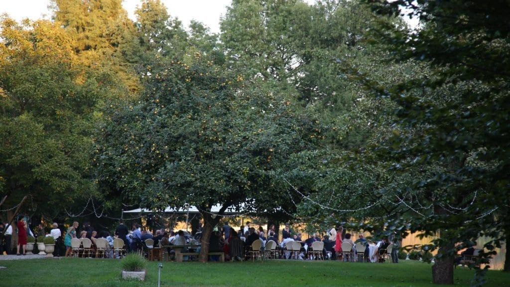 Invitati seduti in giardino sotto agli alberi per il pranzo nuziale